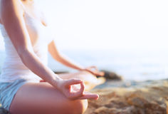 Hand der Frau meditierend in einer Yogahaltung auf Strand Lizenzfreies Stockbild