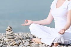Hand der Frau meditierend in einer Yogahaltung auf Strand Lizenzfreie Stockfotos