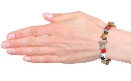 Hand der Frau mit Armbändern auf weißem Hintergrund Lizenzfreie Stockbilder
