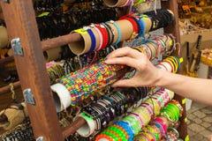 Hand der Frau mit bunten Armbändern auf Stall am Basar Stockfoto