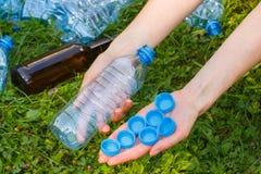 Hand der Frau mit Plastikflasche und Flaschenkapseln, Abfall von Umwelt Lizenzfreie Stockfotografie