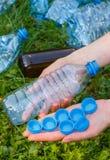 Hand der Frau mit Plastikflasche und Flaschenkapseln, Abfall von Umwelt Lizenzfreie Stockbilder