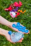 Hand der Frau mit Plastikflasche und Flaschenkapseln, Abfall von Umwelt Stockbilder