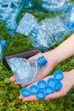 Hand der Frau mit Plastikflasche und Flaschenkapseln, Abfall von Umwelt Lizenzfreies Stockbild