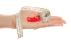 Hand der Frau mit roten Pillen und Bandmaß Lizenzfreies Stockfoto