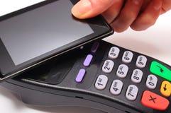 Hand der Frau zahlend mit NFC-Technologie am Handy stockfotografie