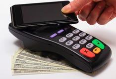 Hand der Frau zahlend mit NFC-Technologie am Handy lizenzfreie stockfotos