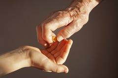Hand der Großmutter und des Enkelkindes mit einer Pille Lizenzfreies Stockbild