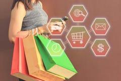 Hand der jungen Frau, die Smartphone mit Hologramm und Einkaufsb hält lizenzfreie stockfotografie