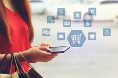 Hand der jungen Frau, die Smartphone und Einkaufstaschen mit holog hält lizenzfreies stockbild