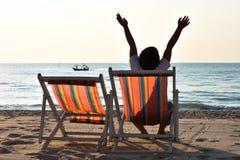 Hand der Jungenerhöhung zwei auf dem Strand Stockbilder