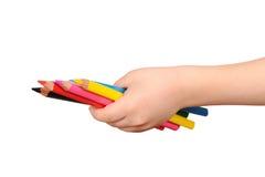 Hand der Kinder hält die bunten Bleistifte an Stockfotos