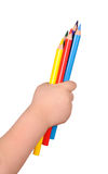 Hand der Kinder hält die bunten Bleistifte an Stockbild