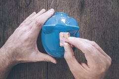 Hand der männlichen Person Geld in Sparschweinspareinlagenkonzept steckend Stockfotografie