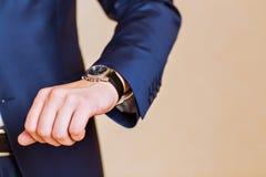 Hand der Männer mit einer Uhr Lizenzfreie Stockbilder