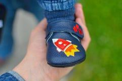 Hand der Mutter Baby ` s Füße halten Stockfotos