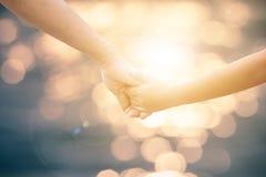 Hand der Mutter und des Kindes, die Hand in Hand die Wärme von Kindern gehen Auf Blurred Hintergrund bokeh natürliches Licht Mess Lizenzfreie Stockfotos