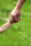 Hand der Muttergesellschafts und des Kindes Stockfoto