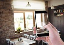 Hand der Person ein Foto eines dinning Raumes mit ihrem Smartphone machend Lizenzfreies Stockfoto
