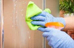 Hand der Reinigungsglasdusche der älteren Frau unter Verwendung microfiber Stoffes und des Reinigungsmittels, Haushaltsaufgabenko Stockfotos
