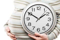 Hand der schwangeren Frau, welche die große Bürowanduhr zeigt Zeit hält Lizenzfreie Stockbilder