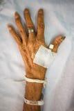 Hand des alten Patienten mit Stecker auf Bett im Krankenhaus Stockbild