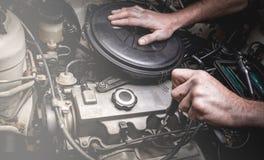 Hand des Automechanikers mit einem Schlüssel Stockbild