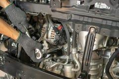 Hand des Automechanikers mit einem Schlüssel Autoreparatur lizenzfreie stockbilder