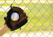 Hand des Baseball-Spielers mit Handschuh und des Balls über Feld Lizenzfreie Stockfotografie