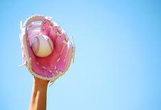 Hand des Baseball-Spielers mit rosa Handschuh und des Balls über blauem Himmel Lizenzfreie Stockfotografie