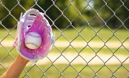 Hand des Baseball-Spielers mit rosa Handschuh und des Balls über Feld Lizenzfreies Stockfoto