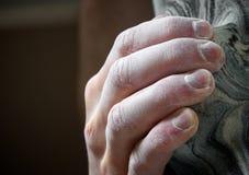 Hand des Bergsteigers, die ein zum künstlichen Einfluss hängt Stockbild