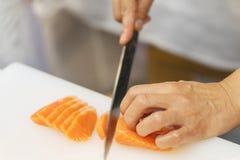 Hand des Chefgebrauchsmessers, das einen frischen Lachs auf einer Ausschnittboa vorbereitet Stockbilder
