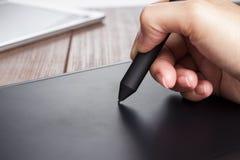 Hand des Designers mit Stift auf Tablette stockbilder