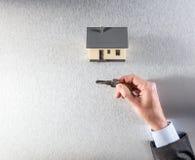 Hand des Geschäftsmannes, des Hauseigentümers oder des Grundstücksmaklervertreters, das Schlüssel gibt Stockfotos