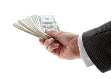 Hand, die Geld gibt Stockfotos