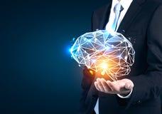 Hand des Geschäftsmannes s, die ganz eigenhändig geschriebes Gehirn hält Stockfotografie