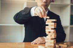 Hand des Geschäftsmannes Stapelspiel der hölzernen Blöcke mit plannin spielend stockbild