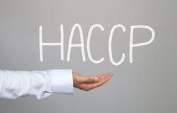 Hand des Geschäftsmannes und die gezeichnete Hand simsen HACCP-System lizenzfreie stockbilder