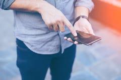 Hand des Geschäftsmannes unter Verwendung beim Ablesen seines Smartphone Lizenzfreies Stockfoto