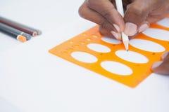 Hand des Geschäftsmannes unter Verwendung der Schablone und des Bleistifts Stockfoto