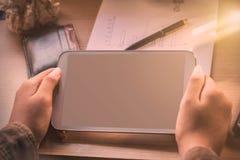 Hand des Haltens der Tablette auf Schreibtisch stockfotos
