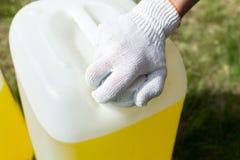 Hand des Handwerkers auf einer Kappe einer Dose Farbe Stockfotos