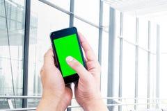 Hand des intelligenten Mobiltelefons des Geschäftsmann-Gebrauches mit Farbenreinheitsschlüssel-Grünschirm auf Hintergrund der Str Stockbild