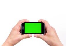Hand des intelligenten Mobiltelefons des Manngebrauches für Schuss ein Foto mit Farbenreinheitsschlüssel-Grünschirm Stockbild