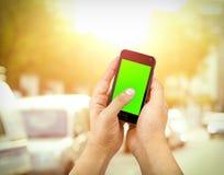 Hand des intelligenten Mobiltelefons des Manngebrauches mit Farbenreinheitsschlüssel-Grünschirm auf Hintergrund der Straße im Fre Stockbild