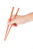 Hand des Jungen, die japanische Ess-Stäbchen anhält Lizenzfreies Stockfoto