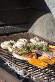 Hand des jungen Mannes irgendein Fleisch und Gemüse grillend Lizenzfreie Stockbilder