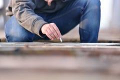 Hand des jungen Mannes, wie Zigarette auf einem alten b auslöschen möchte Stockbild