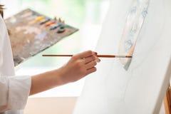 Hand des Künstlers mit Bürstenmalereibild lizenzfreie stockfotografie